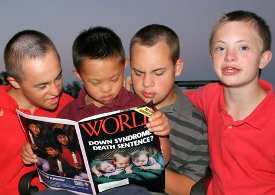 Jesse, 13, Justin, 8, Jonny, 16, and Daniel, 12, read a magazine that has a story in it about the three of them. (Courtesy of the Curtis family)